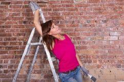 Привлекательный художник женщины на лестнице около кирпичной стены Стоковое фото RF
