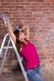 Привлекательный художник женщины на лестнице около кирпичной стены Стоковые Изображения