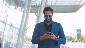Привлекательный человек в вскользь костюме проходит крупным аэропортом и использует его телефон, радостно отвечает к полученное акции видеоматериалы