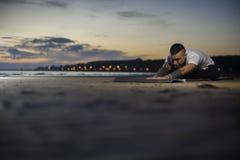 Привлекательный человек делая йогу работает на пляже Стоковое Изображение RF