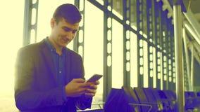 Привлекательный человек использует его мобильный телефон для selfie в авиапорте акции видеоматериалы