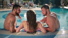Привлекательный человек 2 при молодая красивая женщина ослабляя в бассейне сток-видео