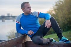 Привлекательный человек сидя на пляже в вечере Стоковые Фотографии RF