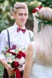 Привлекательный groom детенышей в расчалках сини стоит перед невестой стоковые фотографии rf