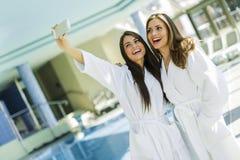 2 привлекательных дамы принимая selfie рядом с бассейном Стоковое фото RF