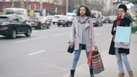 2 привлекательных Афро-американских женщины с хозяйственными сумками вызывая для такси пока приходящ назад от продаж мола акции видеоматериалы