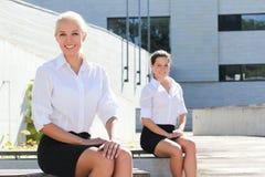 2 привлекательных бизнес-леди сидя над предпосылкой улицы Стоковая Фотография