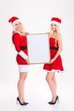2 привлекательных близнеца сестер стоя и держа пустая доска Стоковые Изображения