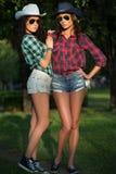 2 привлекательных девушки в ковбойских шляпах и солнечных очках Стоковые Фотографии RF