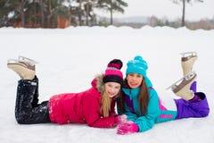 2 привлекательных девушки конькобежца лежа на льде Стоковая Фотография RF