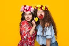 2 привлекательных девушки представляя с цветками Стоковые Фотографии RF