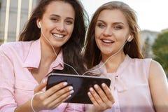 2 привлекательных девушки слушая к музыке Стоковое Фото