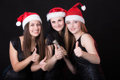 3 привлекательных девушки santa с показом микрофона Стоковая Фотография
