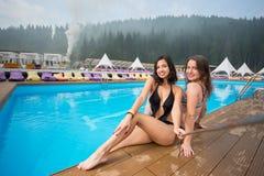 2 привлекательных женщины брюнет нося бикини представляя около бассейна, делая фото selfie с ручкой selfie Стоковое фото RF