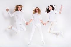 3 привлекательных женщины в белый скакать на белую предпосылку Стоковое фото RF