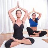 2 привлекательных женщины делая йогу Стоковые Изображения