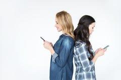 2 привлекательных женщины используя smartphones и положение спина к спине Стоковая Фотография