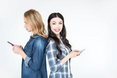 2 привлекательных женщины используя smartphones и положение спина к спине Стоковые Изображения RF