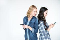 2 привлекательных женщины используя smartphones и положение спина к спине Стоковое Изображение