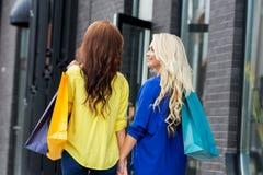 2 привлекательных женщины идя держащ руки вдоль улицы Стоковые Фото