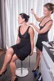 2 привлекательных женщины - одна кладет другой спрея для волос дальше Стоковое Изображение RF