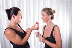 2 привлекательных женщины - одна предлагает клубнику к ее другу Стоковое Изображение RF