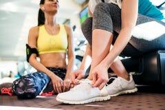2 привлекательных женщины пригонки в спортзале подготавливая для разминки Стоковые Фото