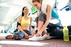 2 привлекательных женщины пригонки в спортзале подготавливая для разминки Стоковая Фотография RF