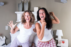 2 привлекательных женщины сидя в кровати и веселить стоковые фотографии rf
