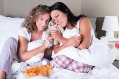2 привлекательных женщины сидя в кровати и мечтать Стоковые Фотографии RF