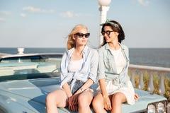 2 привлекательных женщины сидя на автомобиле в лете Стоковое фото RF
