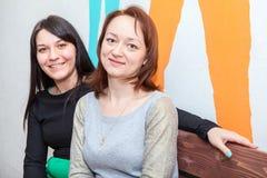 2 привлекательных женщины сидя на стенде совместно Стоковые Изображения