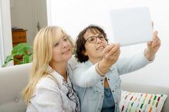 2 привлекательных зрелых женщины с таблеткой Стоковое Фото