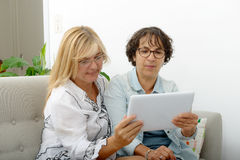 2 привлекательных зрелых женщины websurfing с таблеткой Стоковые Фотографии RF