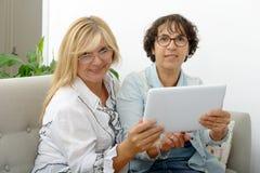 2 привлекательных зрелых женщины websurfing с таблеткой Стоковая Фотография RF