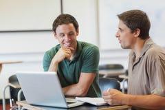 2 привлекательных зрелых студента уча пока сидящ в комнате класса Стоковые Фото