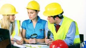 3 привлекательных инженера работая с планами строительства сток-видео