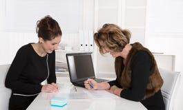 2 привлекательных коллеги дела работая совместно на столе на o Стоковое Фото
