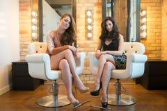 2 привлекательных модели в стульях салона Стоковое фото RF