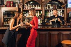 2 привлекательных молодой женщины встречая вверх в пабе для стекла красного вина сидя на встречном усмехаясь одине другого Стоковое Изображение RF
