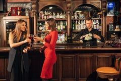 2 привлекательных молодой женщины встречая вверх в пабе для стекла красного вина сидя на встречном усмехаясь одине другого Стоковые Изображения RF