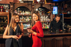 2 привлекательных молодой женщины встречая вверх в пабе для стекла красного вина сидя на встречном усмехаясь одине другого Стоковое Фото