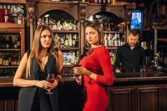 2 привлекательных молодой женщины встречая вверх в пабе для стекла красного вина сидя на встречном усмехаясь одине другого Стоковая Фотография