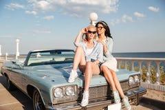 2 привлекательных молодой женщины сидя на автомобиле Стоковое Фото