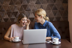 2 привлекательных молодой женщины с компьтер-книжкой в кафе Стоковые Изображения RF