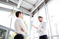 2 привлекательных молодых бизнесмена говоря в офисе Стоковая Фотография