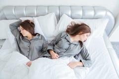 2 привлекательных молодых близнеца сестер спать в кровати Стоковое Фото