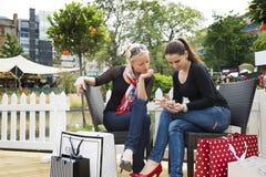 2 привлекательных молодых женских друз наслаждаясь днем вне после успешных покупок Стоковые Изображения