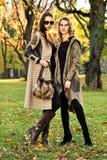 2 привлекательных подруги нося элегантные одежды представляя в парке осени Стоковая Фотография