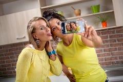 2 привлекательных друз женщины используя мобильный телефон для того чтобы сделать selfi pi Стоковое фото RF